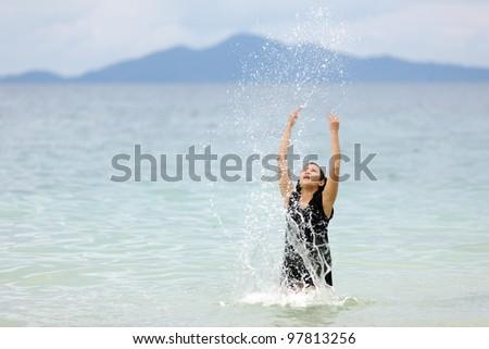 happy woman splashing water in tropical sea, thailand - stock photo
