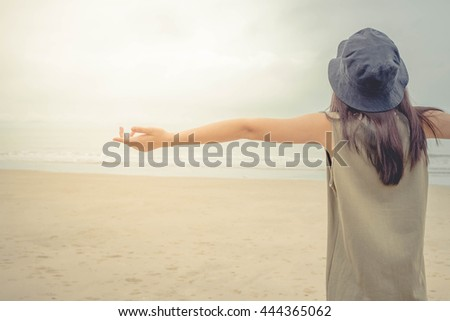 Happy woman standing arms outstretched back and enjoy life on the beach - stock photo