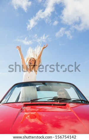Happy woman standing in cabriolet while her boyfriend driving on a sunny day - stock photo