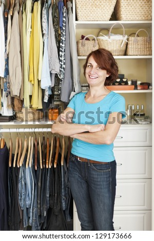 Happy woman standing in front of custom organized closet at home