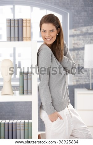 Happy woman standing in living room by book shelf, smiling at camera.? - stock photo