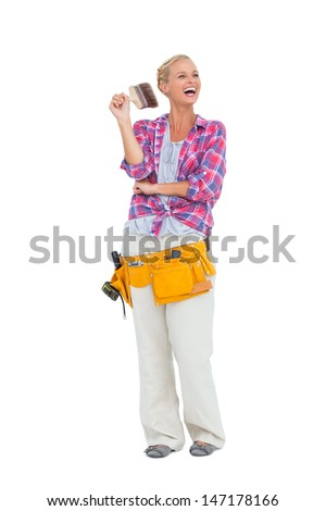 Happy woman standing while holding a paint brush on white background - stock photo