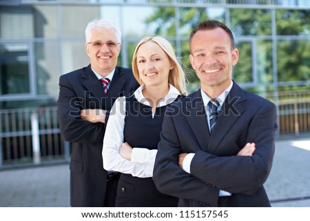 Happy woman standing with arms crossed in a business team