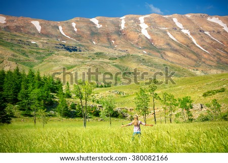 Happy woman standing with raised hands in the fresh green valley near the mountains, enjoying amazing nature of Lebanon - stock photo