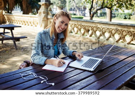 Happy woman student using for learning laptop computer while preparing for lectures in University, smiling hipster girl looking at the camera while working on net-book and write notes in her copybook - stock photo