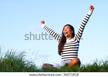 Happy woman student with arms lifted in joy sitting in evening light. Lots of copy space.Beautiful mixed asian / caucasian woman. - stock photo