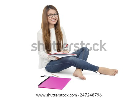 Happy woman studying while sitting on the floor against a white background - stock photo