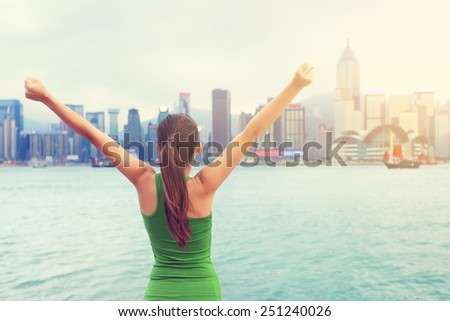 Happy woman success cheering by Hong Kong city skyline with arms raised up outstretched. Successful winner celebrating sunset, Tsim Sha Tsui Promenade and Avenue of Stars in Victoria Harbour, Kowloon. - stock photo
