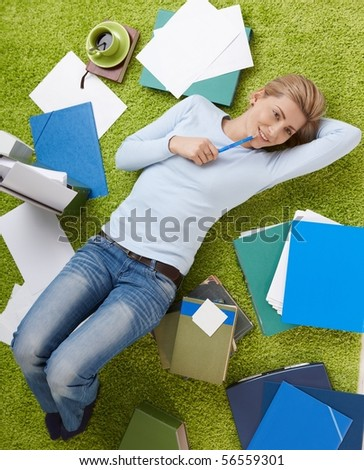 Happy woman surrounded with documents lying on living room floor, daydreaming with hand under head.