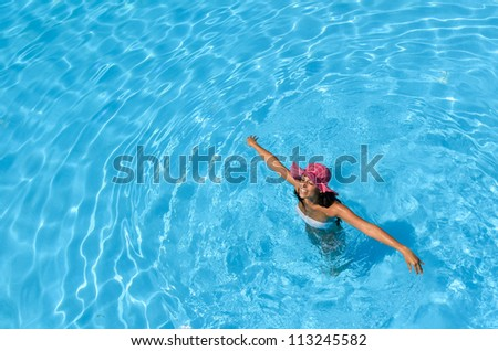 Happy woman swimming in pool on summer holidays. Brunette caucasian model playing into clear water on summer vacation. Copyspace. - stock photo