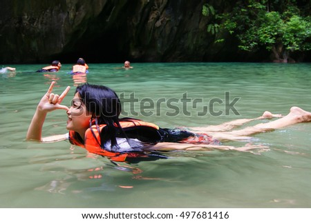 Happy woman swimming with life jacket in the sea