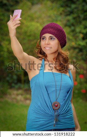 Happy woman takes a picture of herself with her phone, outdoors - stock photo