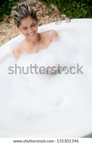 Happy woman taking a bath in a hot tub - stock photo