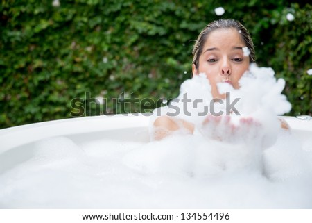 Happy woman taking a bubble bath and being playing with foam - stock photo