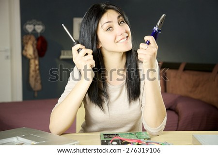 Happy woman taking care of broken technology  - stock photo