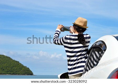 Happy woman taking photos to the sea with smartphone camera on car - stock photo