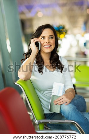 happy woman talking on cell phone while waiting for her flight at airport - stock photo