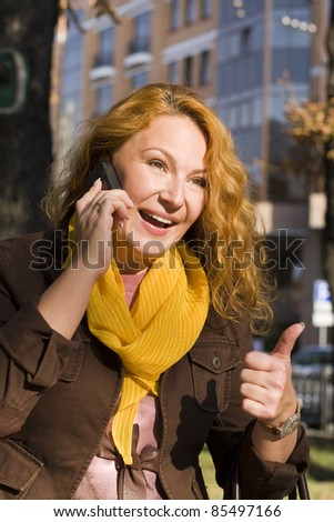 happy woman talking on cell walks down the street - stock photo