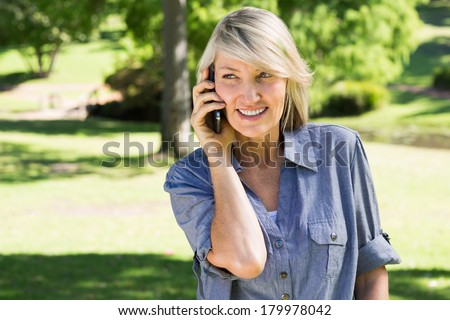 Happy woman talking on mobile phone while looking away in park - stock photo