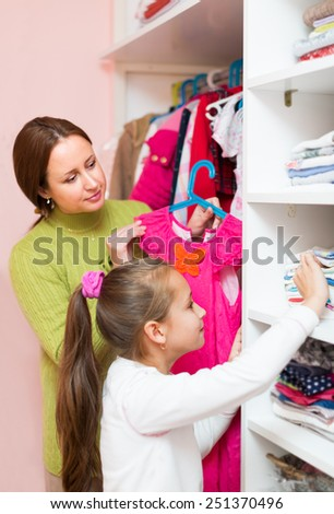 Happy woman teaching and showing  little girl to take care of clothes