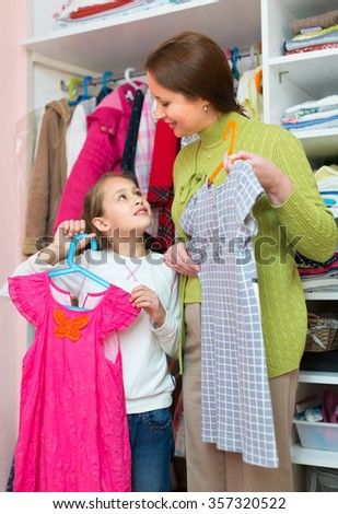 Happy woman teaching little girl to take care of clothes - stock photo