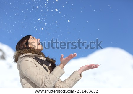 Happy woman throwing snow in the air on winter holidays with a snowy mountain and a blue sky in the background - stock photo