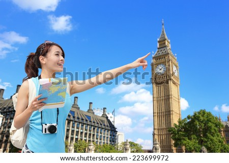 Happy woman travel in London with Big Ben tower, she look map and finger point to building, asian - stock photo