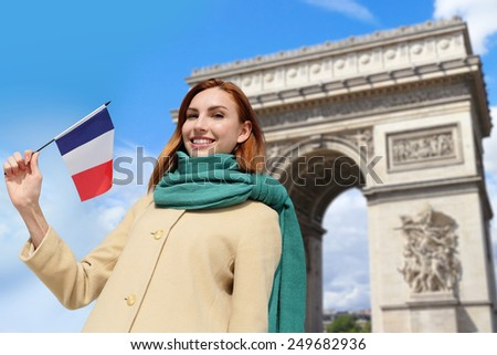 Happy woman travel in Paris, Arc de Triomphe and holding France French flag, caucasian beauty - stock photo