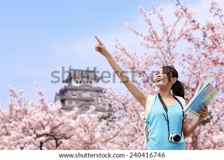 Happy woman traveler enjoy view with sakura cherry blossoms tree and castle on vacation while spring in japan, asian - stock photo