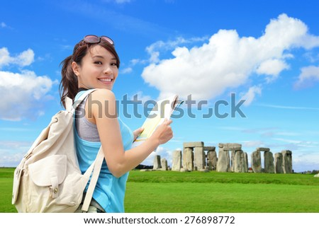 Happy woman traveler in Stonehenge, an ancient prehistoric stone monument , UK. in England,  asian girl - stock photo