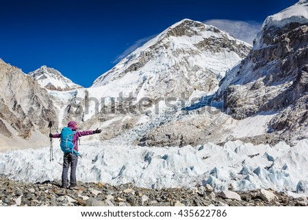 Happy Woman Traveler with Backpack hiking in Mountains. Khumbu valley, Sagarmatha national park, Nepal. mountaineering sport lifestyle concept - stock photo