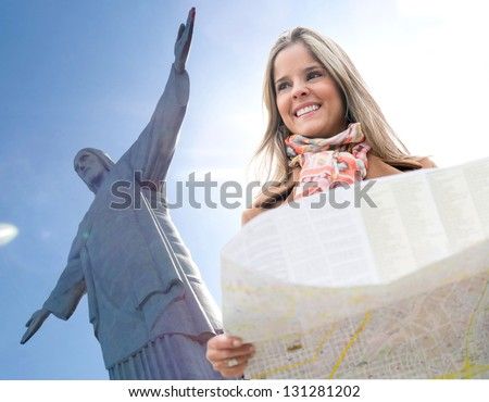 Happy woman traveling to Rio de Janeiro and holding a map - stock photo