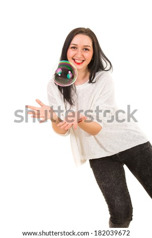 Happy woman trying to catch big soap bubble isolated on white background - stock photo
