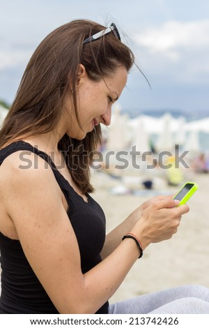 Happy woman typing chat message on cell phone. Brunette girl reading or writing sms on her mobile smartphone. - stock photo