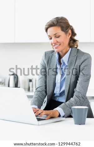 Happy woman typing on laptop in kitchen before work