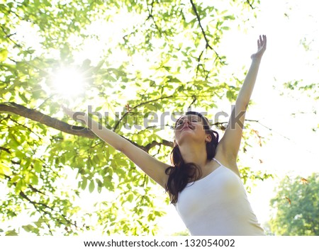 happy woman under a tree in summer - stock photo
