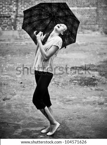 Happy woman under rain with umbrella - stock photo