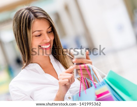 Happy woman using cell phone at a shopping center - stock photo