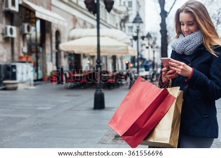 Happy woman using her mobile phone on the street after shopping - stock photo