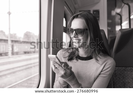 Happy woman using her phone while riding a train. - stock photo