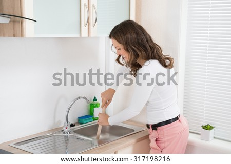 Happy Woman Using Plunger In Kitchen Sink At Home - stock photo