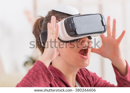 Happy woman using virtual reality headset at home