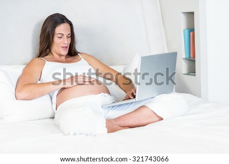 Happy woman video chatting on laptop sitting on bed in house