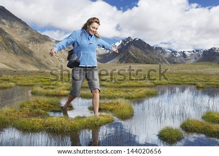 Happy woman walking barefoot through pond against mountains - stock photo