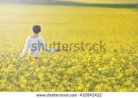 Happy woman walking through a canola field in the summer - stock photo