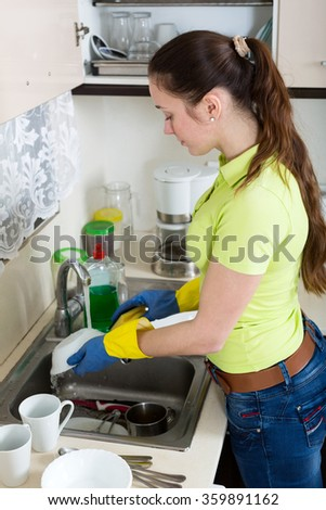 Happy woman washing plates in home kitchen