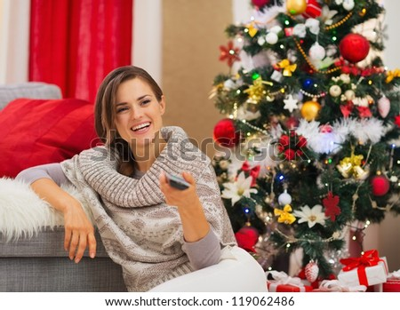 Happy woman watching TV near Christmas tree - stock photo