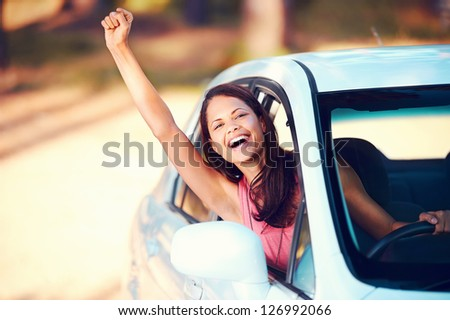 Happy woman waving from drivers seat in car while traveling - stock photo