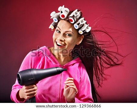 Happy woman wear hair curlers holding  hairdryer. - stock photo
