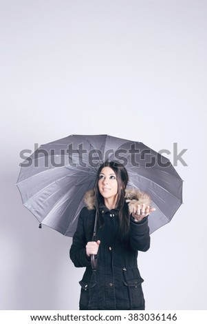 Happy woman wearing a coat, holding an umbrella, over gray background